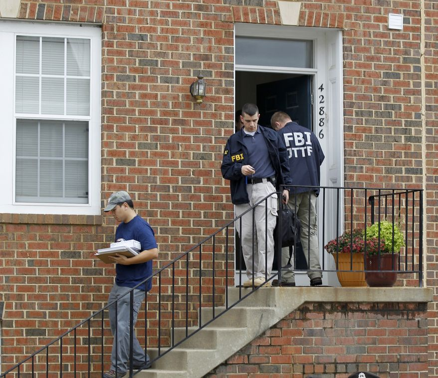 FBI investigators leave the home of Farooque Ahmed in Ashburn, Va., on Wednesday. Mr. Ahmed was arrested and charged with trying to help people posing as al Qaeda operatives planning to bomb subway stations around the nation's capital, the FBI said. (Associated Press)