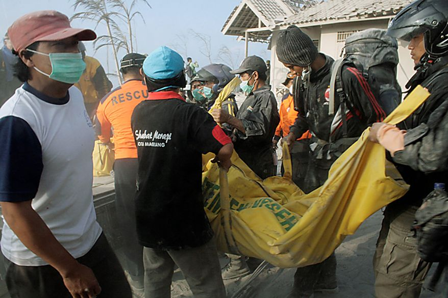 """Rescuers carry the body of a victim of Mount Merapi eruption in Kaliadem, Yogyakarta, Indonesia, Wednesday, Oct. 27, 2010. A volcanic eruption and a tsunami killed scores of people hundreds of miles apart in Indonesia, spasms from the Pacific """"Ring of Fire,"""" which spawns disasters from deep within the Earth. (AP Photo/Slamet Riyadi)"""