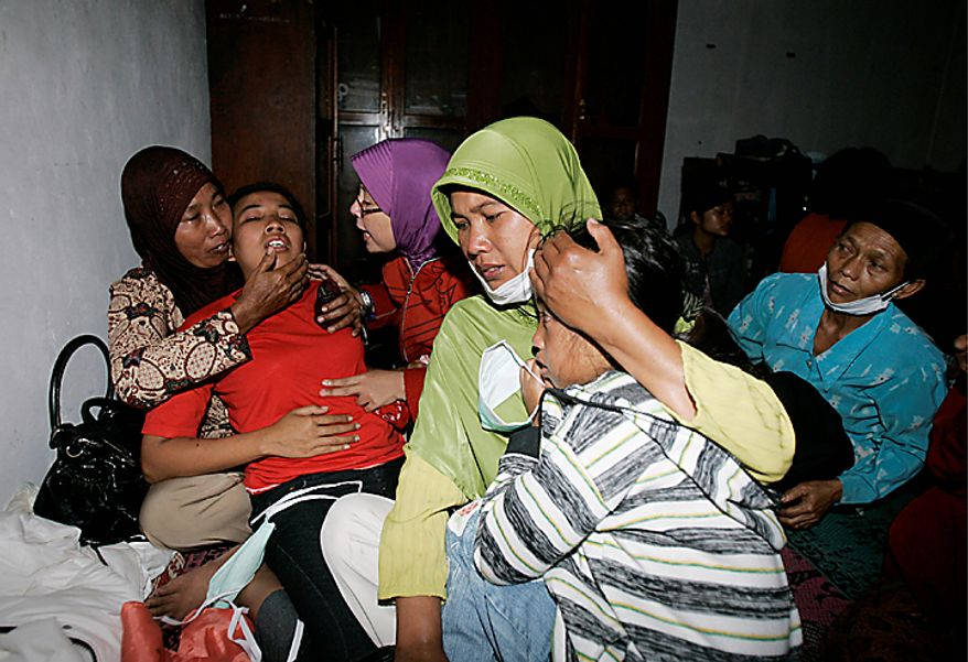 Indonesian women weep upon hearing that their relatives who were killed in Mount Merapi eruption have been identified at a temporary shelter in Umbulharjo, Yogyakarta, Indonesia, Wednesday, Oct. 27, 2010. Rescuers scoured the slopes of Indonesia's most volatile volcano Wednesday after it was rocked by an eruption that spewed clouds of searing ash, killing at least 25 villagers including an old man known as the mountain's spiritual gatekeeper. (AP Photo/Irwin Fedriansyah)