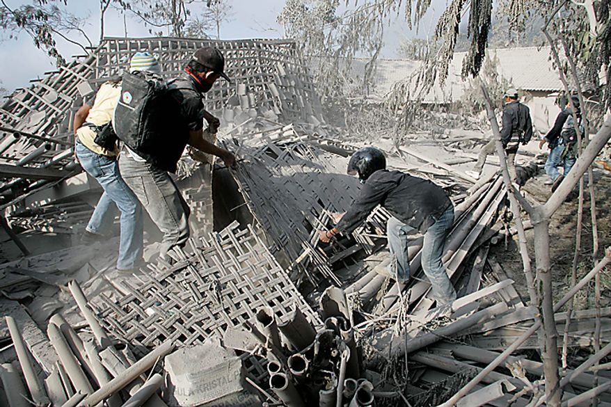 """Rescuers search for victims at a village hit by pyroclastic flows from Tuesday's eruption of Mount Merapi in Kinahrejo, Yogyakarta, Indonesia, Wednesday, Oct. 27, 2010. The volcanic eruption and a tsunami killed scores of people hundreds of miles apart in Indonesia, spasms from the Pacific """"Ring of Fire,"""" which spawns disasters from deep within the Earth. (AP Photo/Trisnadi)"""