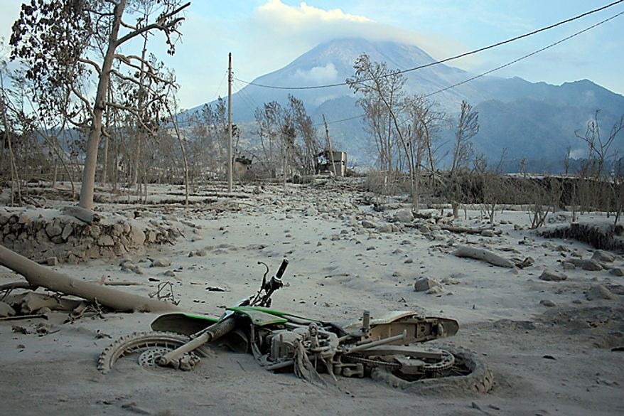 """A motorcycle lies covered by volcanic ash at a village that is hit by pyroclastic flows from Mount Merapi eruption in Kaliadem, Yogyakarta, Indonesia, Wednesday, Oct. 27, 2010. A volcanic eruption and a tsunami killed scores of people hundreds of miles apart in Indonesia, spasms from the Pacific """"Ring of Fire,"""" which spawns disasters from deep within the Earth. (AP Photo/Slamet Riyadi)"""