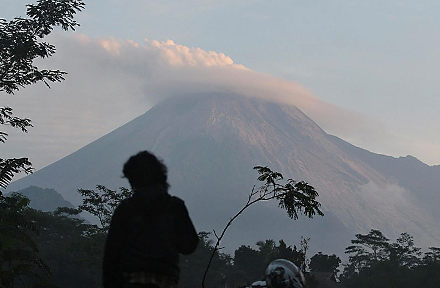 A man watches Mount Merapi as seen from Kaligendol, Yogyakarta, Indonesia, Wednesday, Oct. 27, 2010. Rescuers scoured the slopes of Indonesia's most volatile volcano Wednesday after it was rocked by an eruption that spewed clouds of searing ash, killing at least 25 villagers including an old man known as the mountain's spiritual gatekeeper.  (AP Photo)