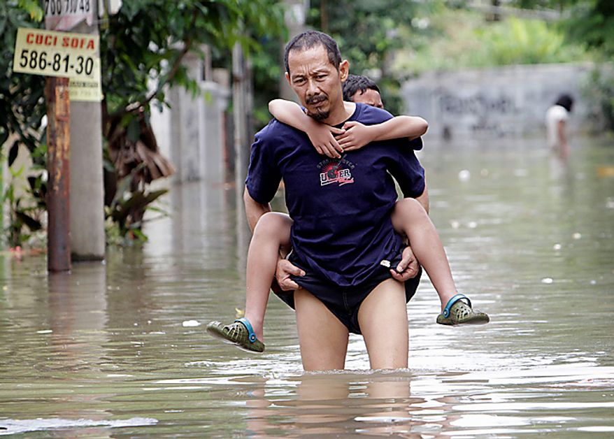 An Indonesian man carries his son through a flooded neighborhood in Tangerang on the outskirts of Jakarta, Indonesia, Wednesday, Oct. 27, 2010. Heavy downpour has caused flooding that occur almost every year in some parts of greater Jakarta due to bad city planning. (AP Photo/Tatan Syuflana)