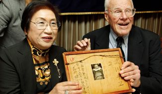 Franklin Hobbs and Chie Takekawa hold a framed letter and a photo of her sister at a press conference in Tokyo on Thursday. As an American GI fighting on Iwo Jima in World War II, Mr. Hobbs found the letter, photo and a now-framed drawing of an air-raid drill (below) on a fallen Japanese soldier in 1945 and took them home as a souvenirs. (Associated Press)