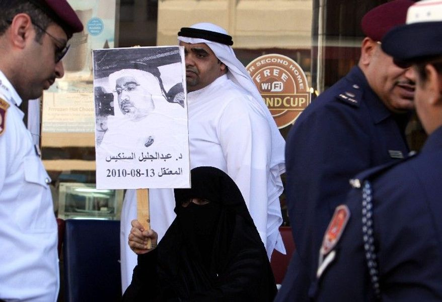 A woman shows support of rights activist Abdel-Jalil Singace outside the courthouse in Manama, where the trial opened for him and two dozen others accused of plotting against Bahrain's rulers. (Associated Press)