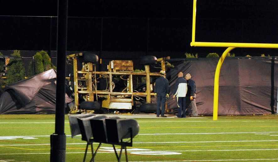 Emergency personnel examine the spot where a scissor-lift tower in which student Declan Sullivan had been taping Notre Dame football practice toppled in heavy winds. (Notre Dame Observer via Associated Press)