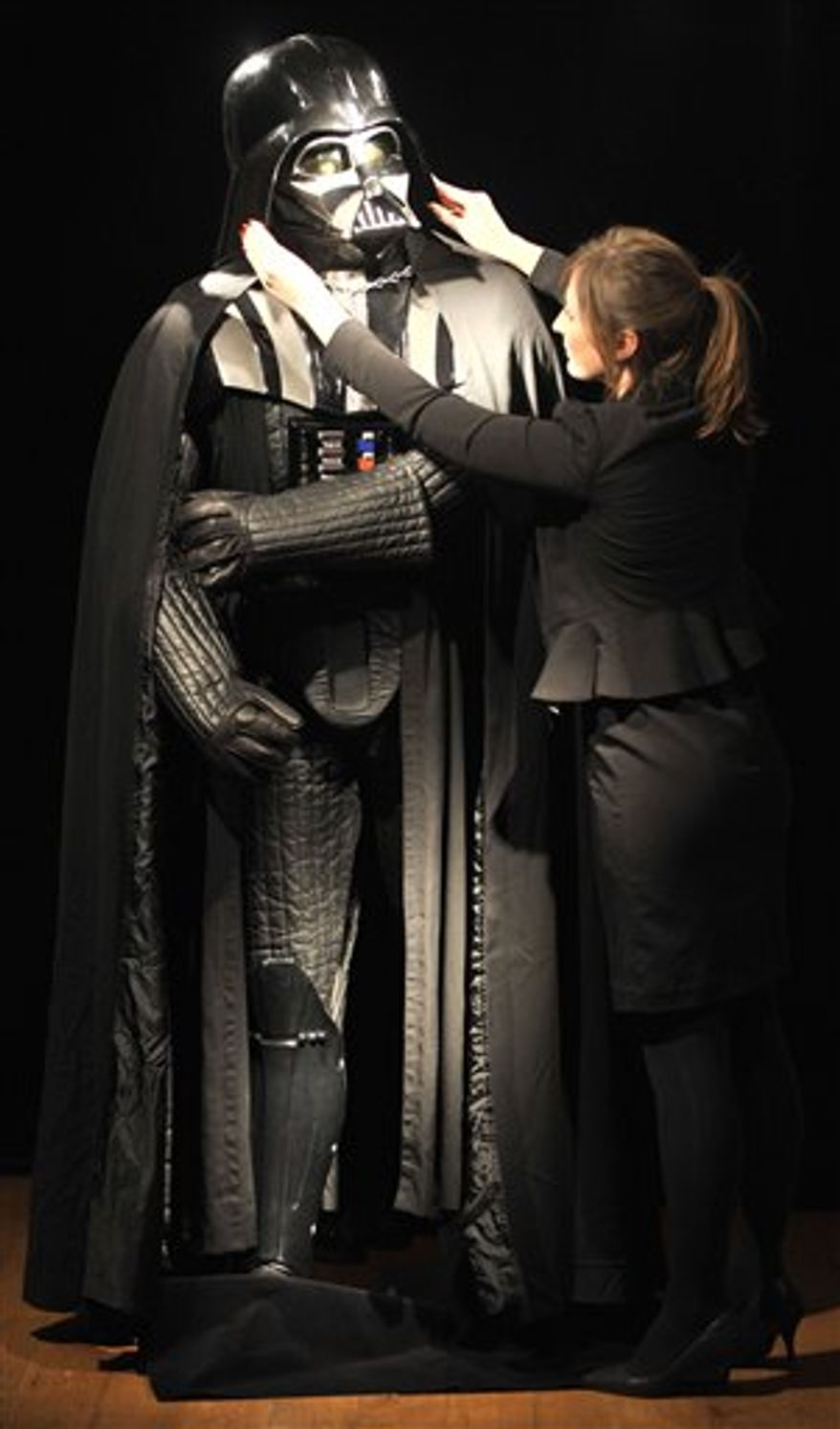 Christie's employee Caitlin Graham poses with a Darth Vader costume in London, Wednesday, Oct. 27, 2010. The helmet, mask, shoulder armour and shin guards of the costume have been produced for the second Star Wars movie 'The Empire Strikes Back', released in 1980. On November 25, 2010 the costume will be offered at Christie's South Kensington and is expected to realise 160,000 GBP to 230,000 GBP.(AP Photo/Lennart Preiss)