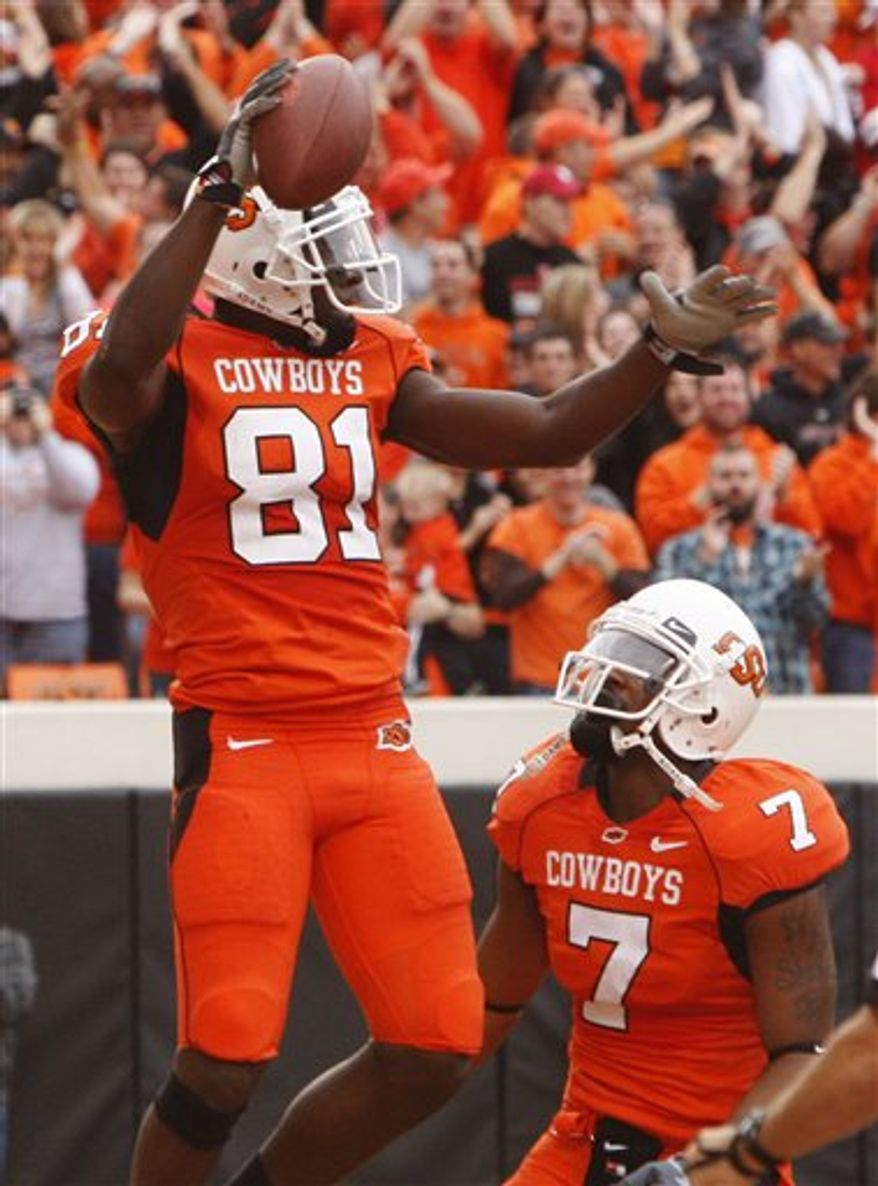 Oklahoma State wide receiver Justin Blackmon, left, celebrates with teammate Michael Harrison following a touchdown against Nebraska in the second quarter of an NCAA college football game, Saturday, Oct. 23, 2010, in Stillwater, Okla. (AP Photo/Sue Ogrocki)
