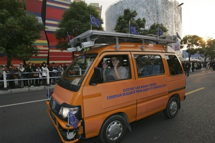 Two driverless vehicles, in orange, equipped with laser scanners and cameras that work in concert to detect and help avoid obstacles, travel on the Shanghai Expo site to attend the official celebration of their arrival Thursday Oct. 28, 2010 in Shanghai, China. A team of Italian engineers launched what has been billed as the longest-ever test drive of driverless vehicles: a 13,000-kilometer (8,000-mile), three-month road trip from Italy to China. (AP Photo)