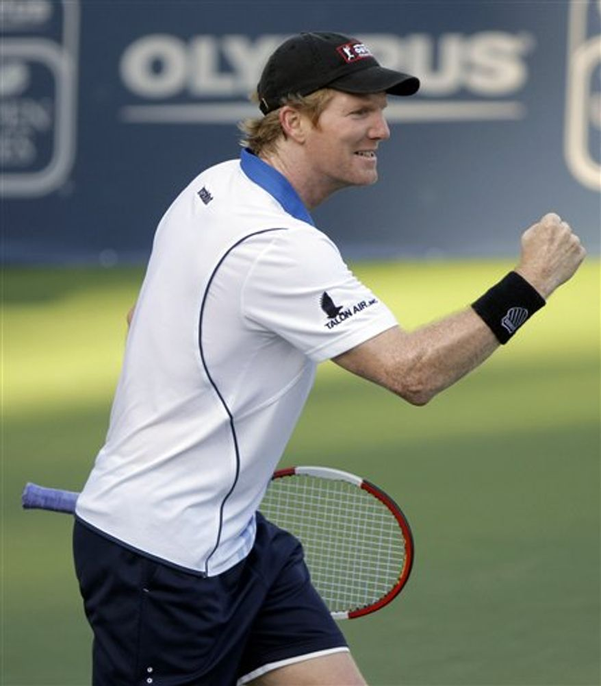 FILE - This Oct. 27, 2010, file photo shows Jim Courier holding a replica of the Davis Cup,  during a news conference in New York.  Courier is part captain, part trainer heading into his first match leading the U.S. Davis Cup team. (AP Photo/Kathy Willens, File)