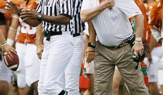 Texas head coach Mack Brown, right, complains to officials during the first half of an NCAA college football game against Iowa State, Saturday, Oct. 23, 2010, in Austin. Iowa State won 28-21. (AP Photo/Darren Abate)