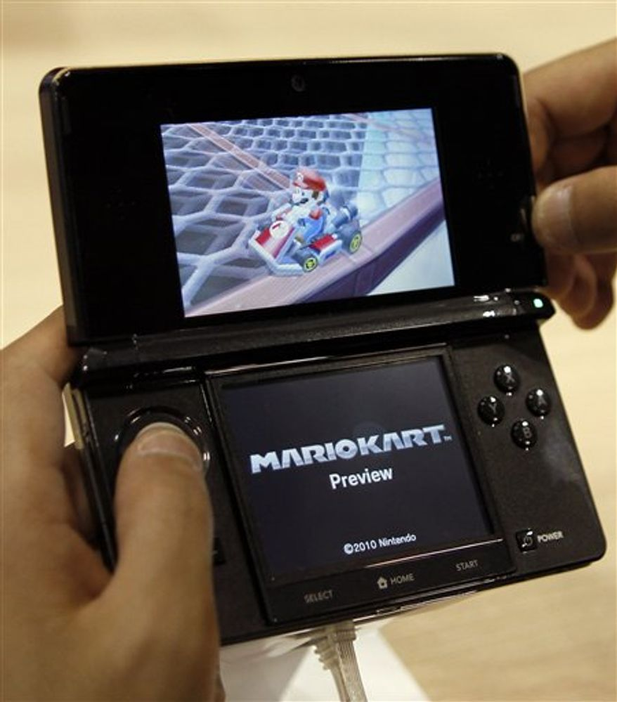 File - In this Sept. 29, 2010 file photo, a visitor operates a Nintendo 3DS featuring 3-D imagery during a press conference by Nintendo Co. President Satoru Iwata where he launches the new game machine which will hit the Japanese market in Feb., 2011 in Chiba near Tokyo, Japan. Nintendo reported Thursday, Oct. 28, 2010, it sank into the red for the fiscal first half, battered by a rising yen that hurts exports and plunging sales as demand for its game machines ran out of steam. (AP Photo/Shuji Kajiyama, File)