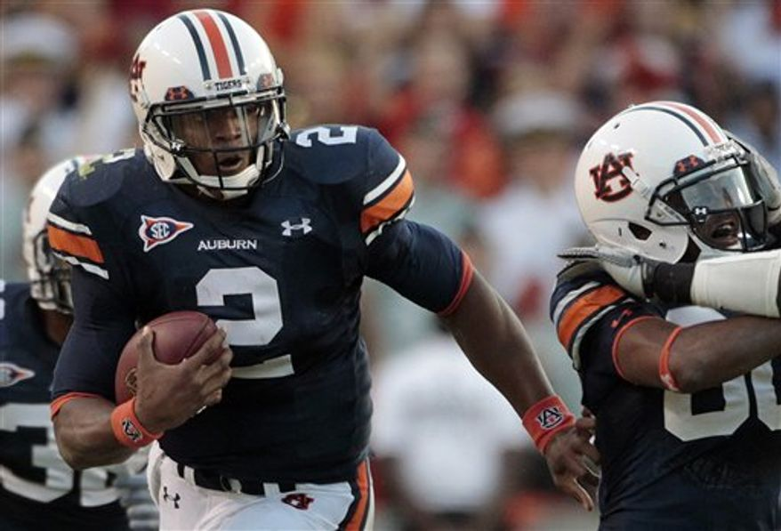 Auburn quarterback Cameron Newton (2) runs for a first down in the fourth quarter in an NCAA college football game against LSU at Jordan-Hare Stadium in Auburn, Ala., Saturday, Oct. 23, 2010.  Newton had 217 yards rushing in the 24-17 win. (AP Photo/Dave Martin)