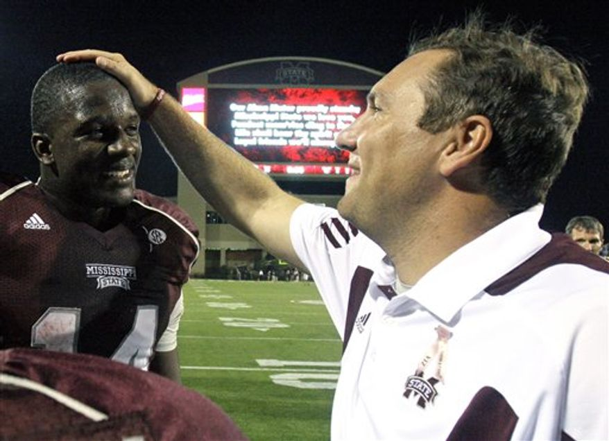 In this photo taken Oct. 23, 2010, Mississippi State quarterback Chris Relf is congratulated by football coach Dan Mullen after their NCAA college football game against UAB in Starkville, Miss. Now No. 23 Mississippi State survived a close game to win 29-24. Relf completed 8 of 19 passes for 107 yards and a touchdown. (AP Photo/Rogelio V. Solis)