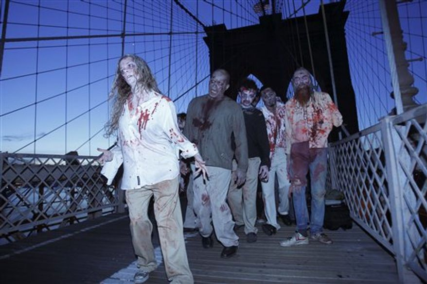 """A bicyclist and jogger pass a group of zombies posing for pictures on the Brooklyn Bridge in New York, Tuesday, Oct. 26, 2010.  The stunt was part of a campaign in 26 cities worldwide promoting the Halloween premiere of the AMC television series """"The Walking Dead."""" (AP Photo/Seth Wenig)"""