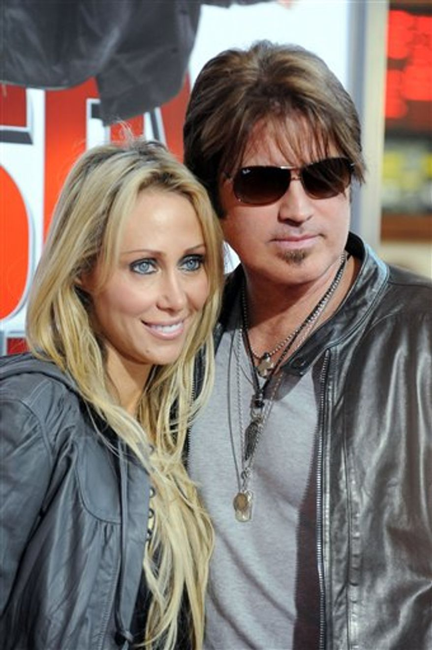 "FILE - In this April 23, 2009 file photo, singer and actress Miley Cyrus, left and her father musician Billy Ray Cyrus,  arrive for the British Premiere of the film '""Hannah Montana"",  at a Leicester Square cinema, in London.  (AP Photo/Joel Ryan, file)"