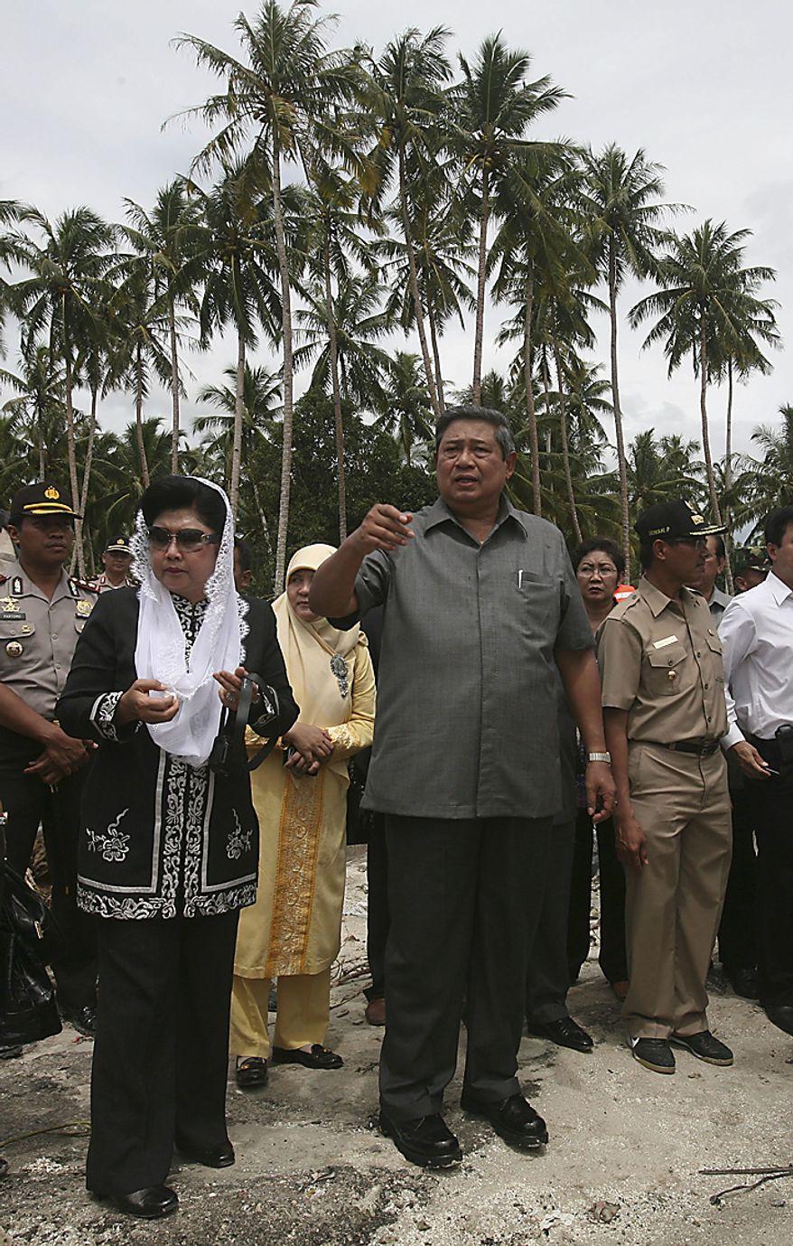 Indonesia President Susilo Bambang Yudhoyono,right, and his wife Kristiani Herawati, left, survey damages on the tsunami-ravaged Pagai island, in Mentawai Islands, Indonesia, Thursday, Oct. 28, 2010.(AP Photo/Achmad Ibrahim)