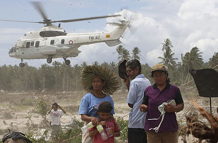 Tsunami survivors turn their face away from down wash created by a helicopter at Parorogat, Pagai island,West Sumatra, Indonesia, Thursday, Oct. 28, 2010. (AP Photo/Achmad Ibrahim)