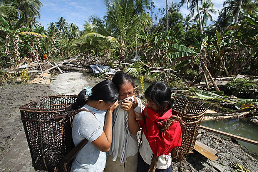 A woman who lost her house and husband in the earthquake-triggered tsunami weeps with her daughters on Pagai island, in Mentawai Islands, Indonesia, Thursday, Oct. 28, 2010. (AP Photo/Tundra Laksamana)
