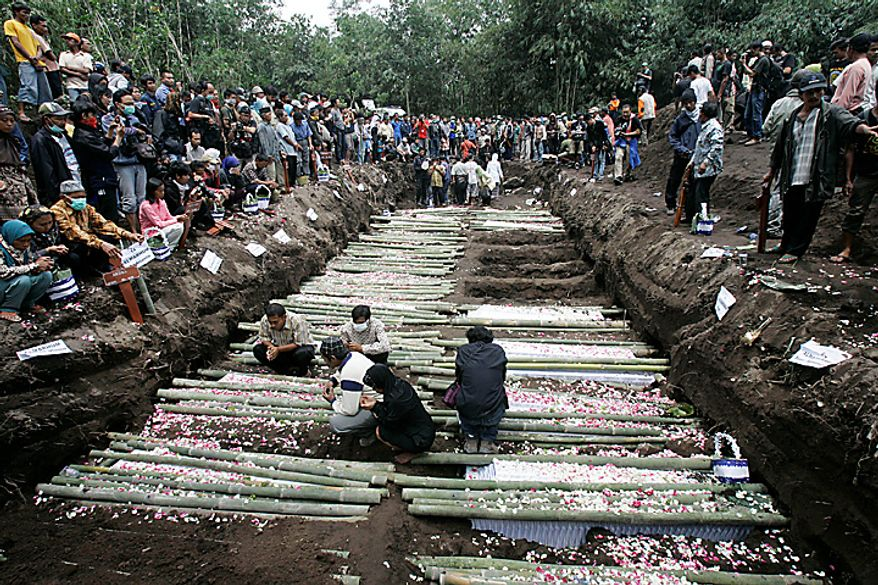 Relatives pray in the grave for the victims of Mount Merapi eruption during a mass burial in Umbulharjo, Yogyakarta, Indonesia, Thursday, Oct. 28, 2010. (AP Photo/Irwin Fedriansyah)
