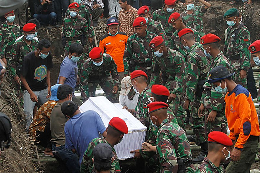 Indonesian soldiers carry the coffin bearing a victim of Mount Merapi eruption during a mass burial in Umbulharjo, Yogyakarta, Indonesia, Thursday, Oct. 28, 2010. (AP Photo/Irwin Fedriansyah)