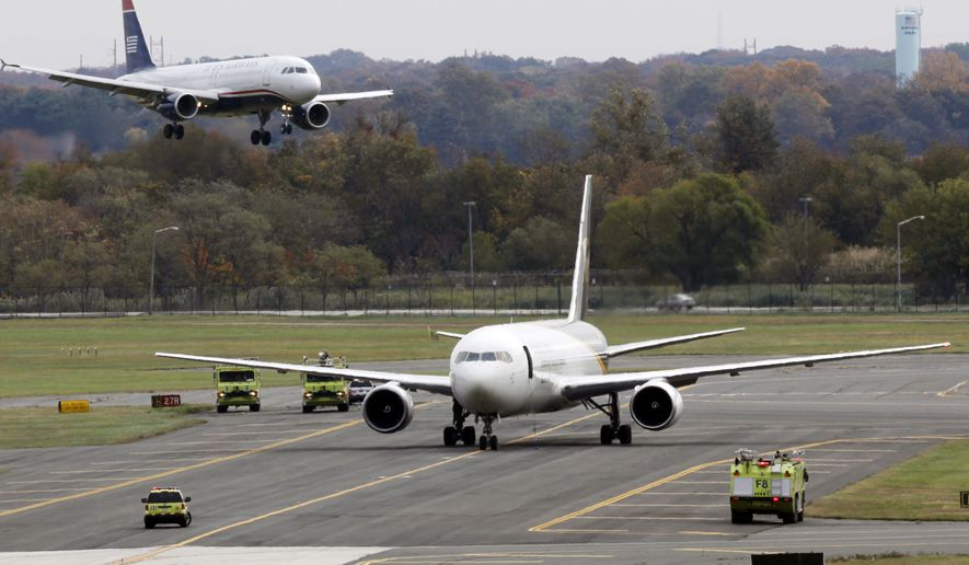 A jet lands near a United Parcel Service plane that is isolated on a runway at Philadelphia International Airport in Philadelphia, Friday, Oct. 29, 2010. Law enforcement officials are investigating reports of suspicious packages on cargo planes in Philadelphia and Newark, N.J. (AP Photo/Matt Rourke)
