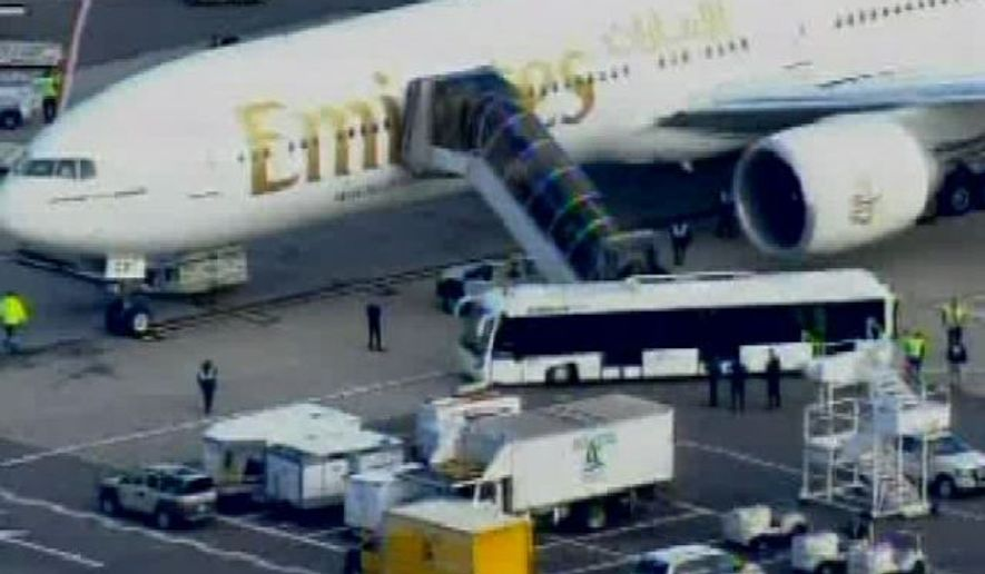 In this frame grab taken from WABC-TV video, passengers disembark an Emirates airliner into an awaiting bus at John F. Kennedy International Airport in New York, Friday Oct. 29, 2010, after having been escorted from the Canadian border to New York City by two military fighter jets. U.S. officials said the plane was being escorted to JFK as a precautionary move since it carried a package from Yemen. (AP Photo/WABC-TV)