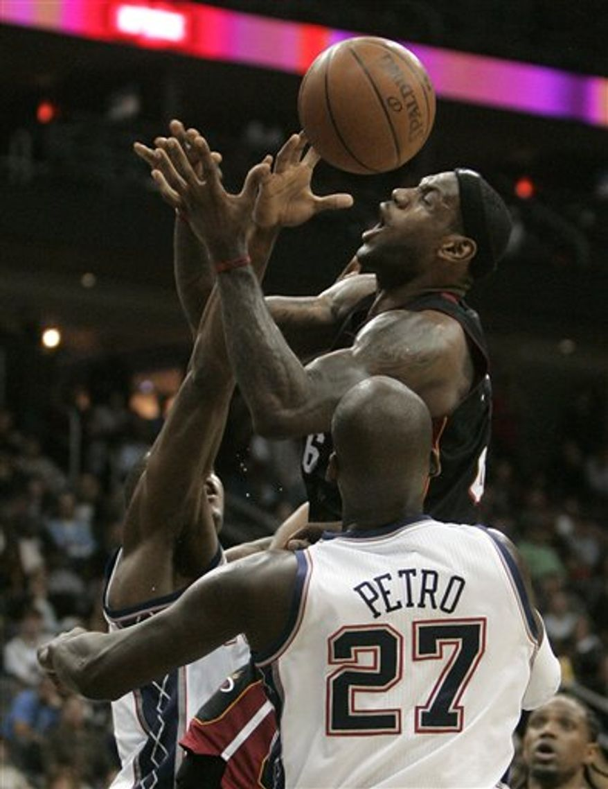 Miami Heat's LeBron James (6), is fouled by New Jersey Nets' Derrick Favors, left, as Nets' Johan Petro (27), of France, looks on in the third quarter during an NBA basketball game in Newark, N.J., Sunday, Oct. 31, 2010. The Heat defeated the Nets 101-78. (AP Photo/Rich Schultz)