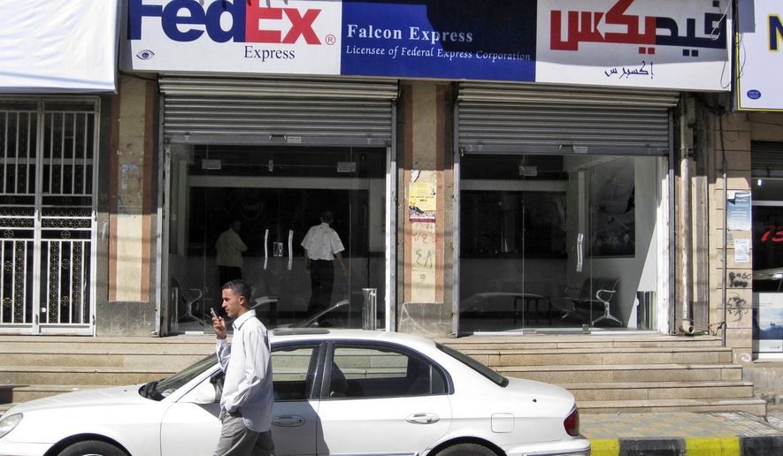 A Yemeni man speaks on his mobile phone while walking past an office of Falcon Express, the partner service provider of FedEx, in the Yemeni capital, San'a, on Saturday, Oct. 30, 2010. U.S. and Yemeni authorities are searching for those who shipped two bombs from Yemen bound for Chicago-area synagogues in a brazen plot that heightened fears of a renewed al Qaeda terror offensive against the United States and other Western countries. (AP Photo)