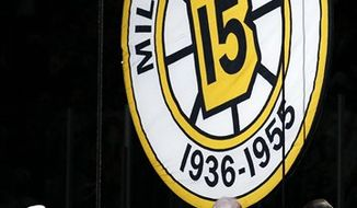 Milt Schmidt, left, a former Boston Bruin and a hockey Hall of Famer, gets the honor of raising his number to the rafters for the first time, prior to the Bruins' NHL hockey game against the Toronto Maple Leafs in Boston on Thursday, Oct. 28, 2010. (AP Photo/Winslow Townson)