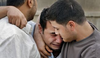An Iraqi man is consoled by friends at the scene of a car bomb attack Monday in front of a Syrian Catholic Church in Baghdad. Islamic militants held about 120 Iraqi Christians hostage in a church Sunday before security forces freed them, ending a standoff that left dozens of people dead. (Associated Press)