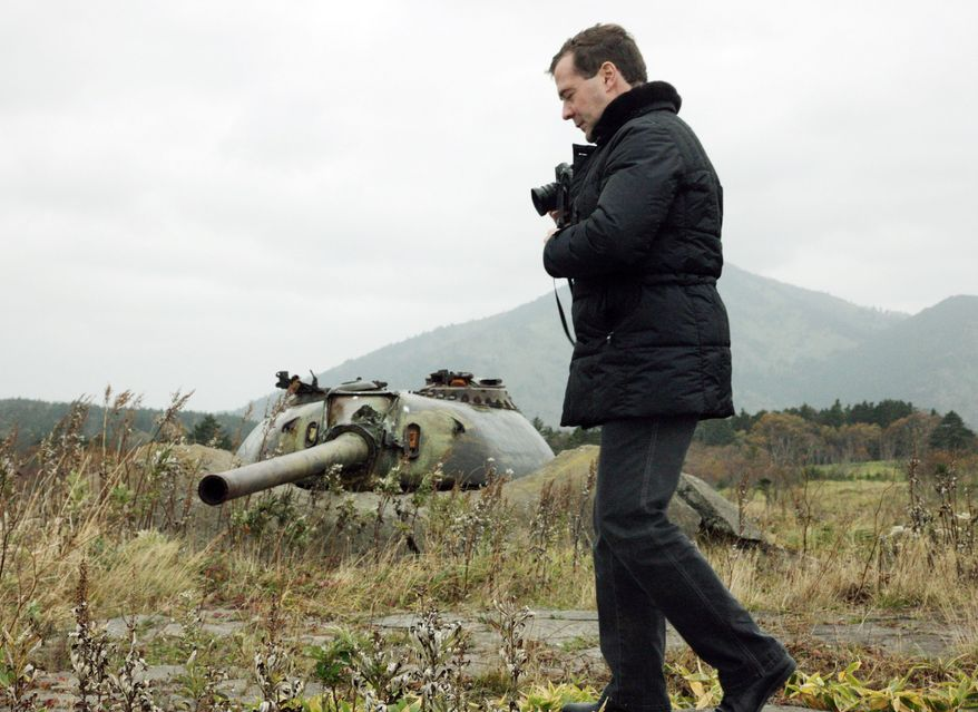 Russian President Dmitry Medvedev walks the land of what his country calls the southern Kurils and Japan calls the Northern Territories. He promised to improve the standard of living there. (RIA Novosti Kremlin via Associated Press)