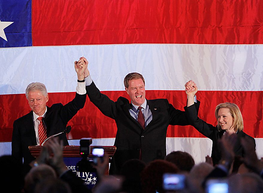 Former President Bill Clinton, left, Rep. Scott Murphy, D-NY, center, and Sen. Kirsten Gillibrand, D-NY, raise their arms during a campaign rally in Saratoga Springs, N.Y., Monday, Nov. 1, 2010. (AP Photo/Mike Groll)
