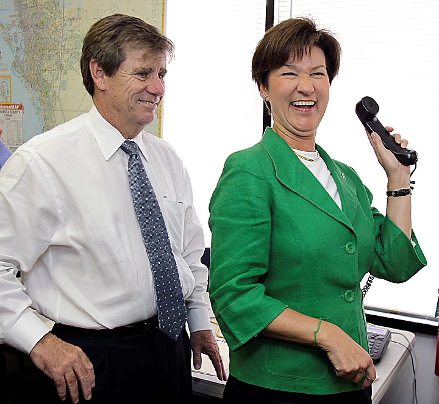 Florida Democratic gubernatorial candidate Alex Sink, right, laughs with running mate Rod Smith after a telephone call interrupted her speech to campaign workers at the Sarasota County Democratic Party office Monday, Nov. 1, 2010, in Sarasota, Fla. Sink is running against Republican Rick Scott. (AP Photo/Chris O'Meara)