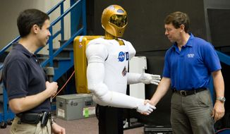 Discovery shuttle astronaut-physician Michael Barratt shakes hands with Robonaut 2 on Aug. 4 at Johnson Space Center. Ron Diftler, Robonaut project manager, is at left. Robonaut 2 and Mr. Barratt are set to liftoff Wednesday. (NASA photograph via Associated Press)