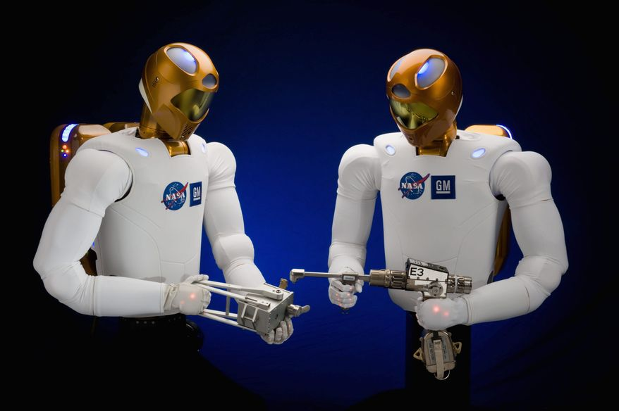 Robonaut 2 robots are seen in July 2009 in Houston. The Robonaut 2 taking off Wednesday for the International Space Station will stay there until the station stops operating after 2020. (NASA photograph via Associated Press)