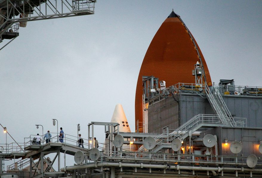 NASA workers walk along a platform on the service structure next to space Shuttle Discovery on Pad 39A at the Kennedy Space Center in Cape Canaveral, Fla. Discovery's final launch was delayed until Thursday. (Associated Press)
