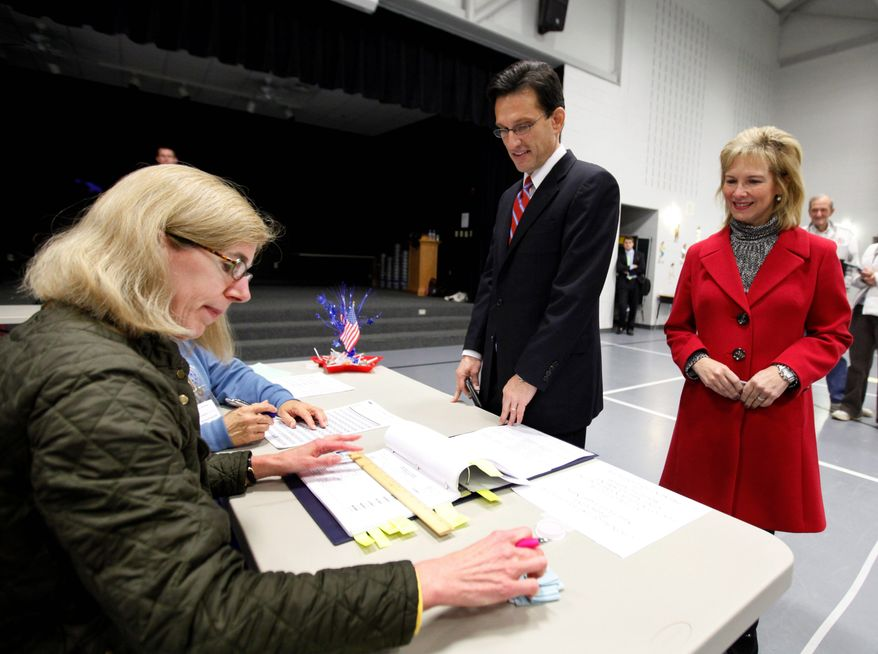 ASSOCIATED PRESS PHOTOGRAPHS Poll worker Wendy Wurlitzer checks the voter registration rolls as Rep. Eric Cantor and his wife, Diana, vote at Rivers Edge Elementary School on Tuesday.