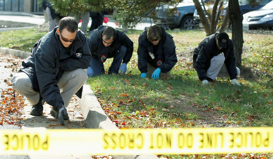 FBI investigators search for evidence near a U.S. Coast Guard recruiting office in Woodbridge, Va. Police in Northern Virginia said at least one shot was fired overnight at the recruiting office, damaging glass. (Associated Press)