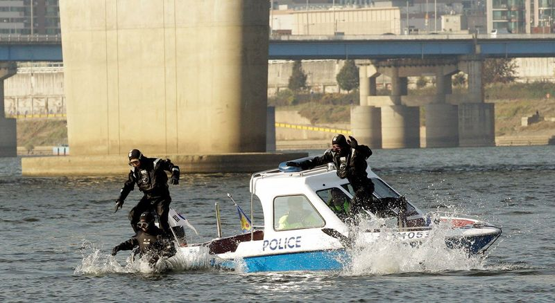 South Korean police officers jump into the Han river while patrolling for possible terrorist activity before next week's G-20 meeting in Seoul. (Associated Press)