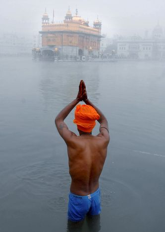 A Sikh devotee practices his faith at the Golden Temple, Sikhs' holiest shrine, in Amritsar, India, in January. President Obama's trip to India this week won't include a visit to the temple after all. (Associated Press)