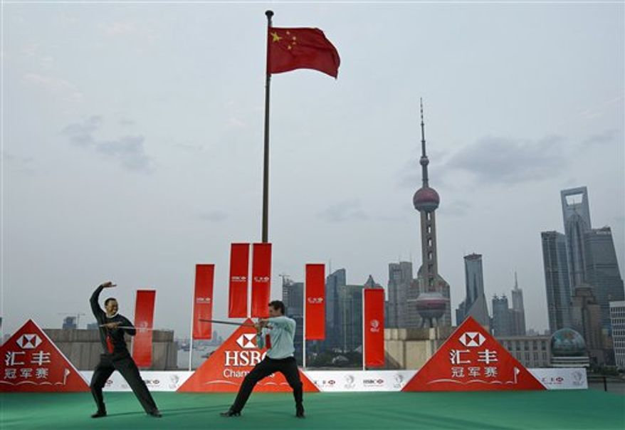 Tiger Woods of the U.S., left, and Lee Westwood of Britain, right, performs the Chinese martial art of taichi on a stage against the Pudong Financial District during a photo call in Shanghai, China Tuesday, Nov. 2, 2010. (AP Photo/Andy Wong)