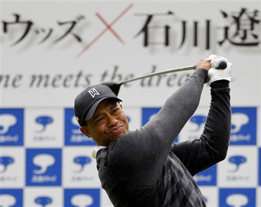 Tiger Woods of the U.S. tees off as he plays with Ryo Ishikawa of Japan during their 9-hole golf match for a television event at Yokohama Country Course, near Tokyo, Japan, Monday, Nov. 1, 2010. (AP Photo/Shuji Kajiyama)