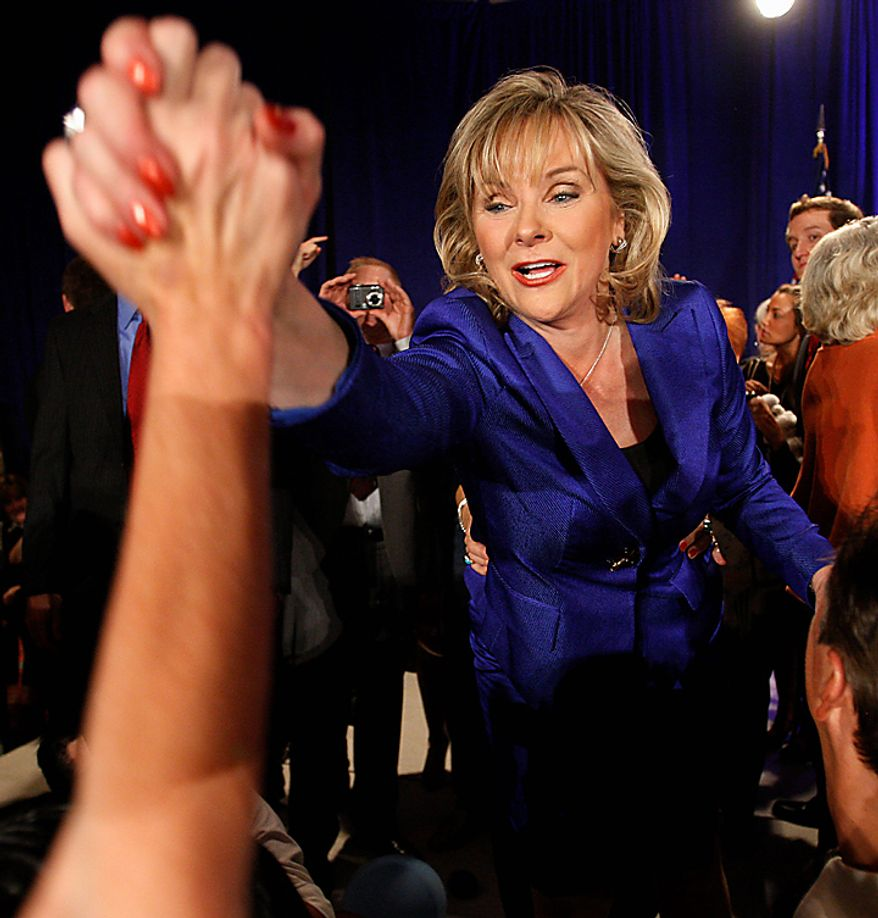 Oklahoma Governor-elect Mary Fallin reaches from the stage to greet supporters at her victory party in Oklahoma City, Tuesday, Nov. 2, 2010. Fallin leveraged her two decades of roots in Oklahoma politics to energize Republican voters and smash a gender barrier Tuesday, becoming the state's first female governor and finishing a GOP sweep of state government. (AP Photo/Sue Ogrocki)