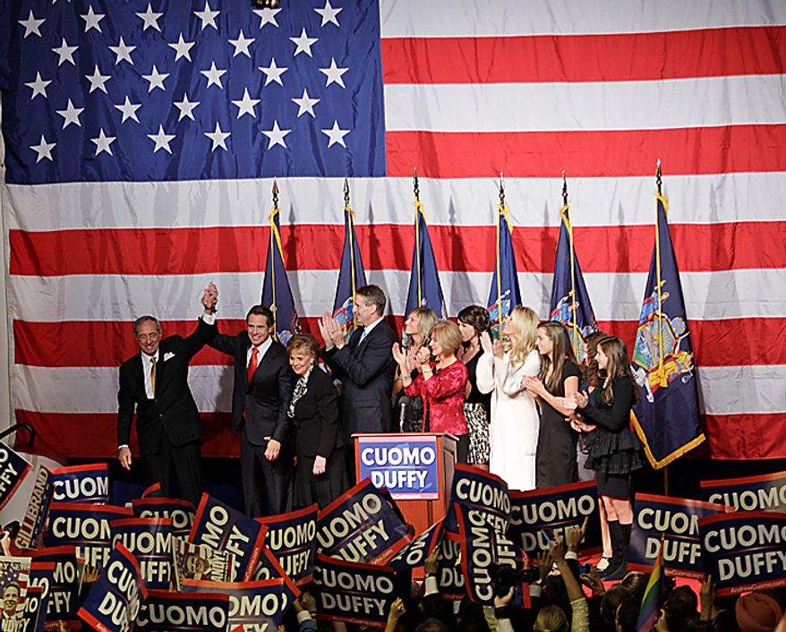 New York Governor-elect Andrew Cuomo, second left, clasps hands with his father, former New York Gov. Mario Cuomo, while giving his victory speech in New York on Tuesday, Nov. 2, 2010. (AP Photo/Frank Franklin II)