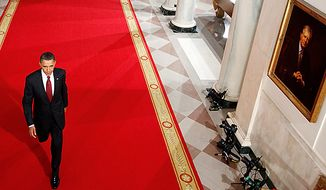 President Barack Obama walks past a portrait of former President Jimmy Carter, right, in the Cross Hall of the White House in Washington, Wednesday, Nov. 3, 2010, as he headed to the East Room for a news conference the day after the midterm elections. (AP Photo/Charles Dharapak)
