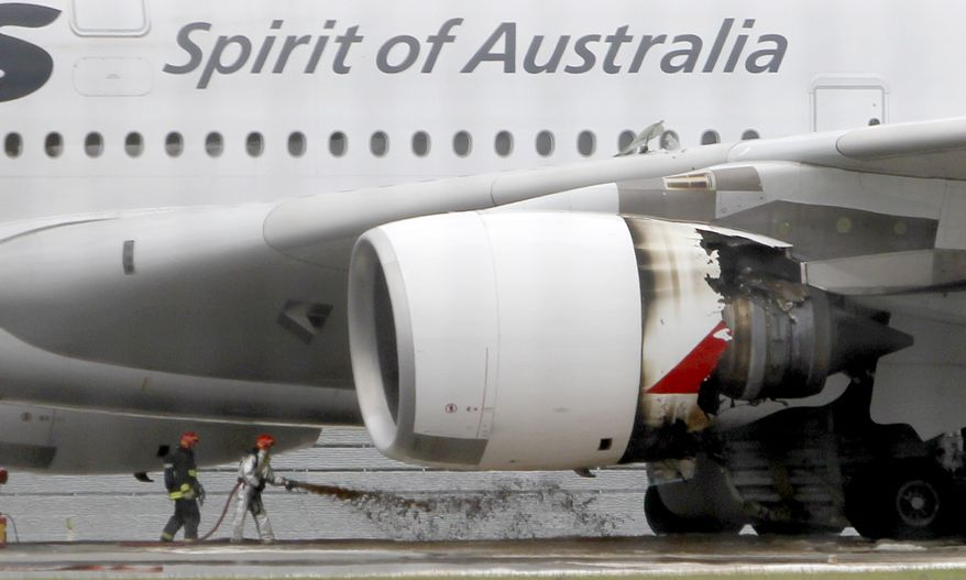 ** FILE ** Firefighters surround a Qantas Airbus A380 superjumbo jet after it made an emergency landing with 459 people aboard at Singapore's Changi International Airport after having engine problems on Thursday, Nov. 4, 2010. (AP Photo/Wong Maye-E, File)