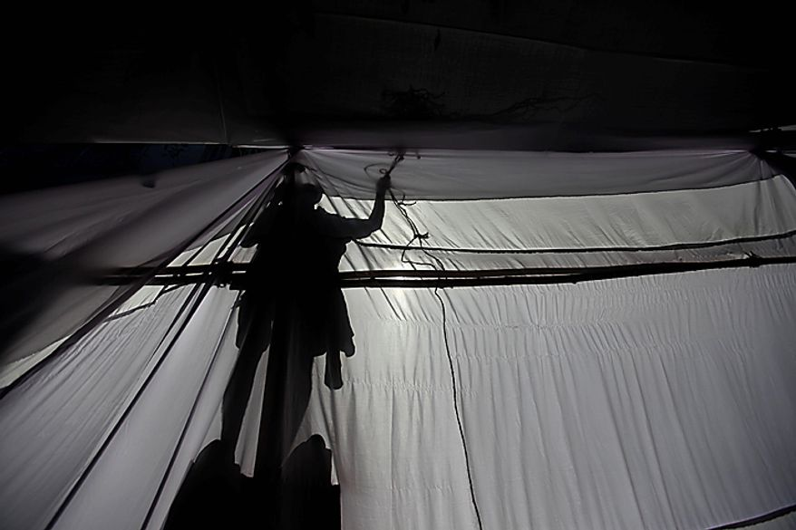 A worker puts up a tent outside Mani Bhavan, the Mumbai residence of Mahatma Gandhi, in Mumbai, India, Thursday, Nov. 4, 2010. President Barack Obama is scheduled to visit Mani Bhavan during his trip to the city. (AP Photo/Rafiq Maqbool)