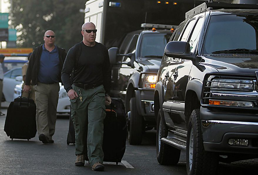 Members of a U.S. security team arrive at the Taj Mahal hotel in Mumbai, India, Thursday, Nov. 4, 2010. President Barack Obama is scheduled to stay at the hotel on Nov. 6. The 107-year-old Taj Mahal hotel reopened for business in August, nearly two years after a siege that left 166 people dead across the city, including 31 at the hotel. (AP Photo/Rafiq Maqbool)