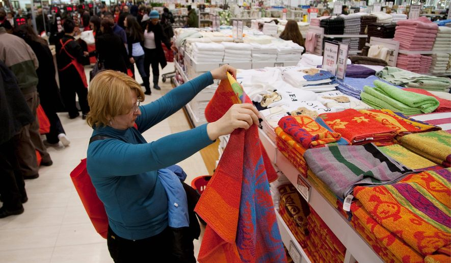 A shopper at Century 21 department store in New York examines beach towels. Americans are being precise in how they shop, regardless of what they are buying. (Associated Press)